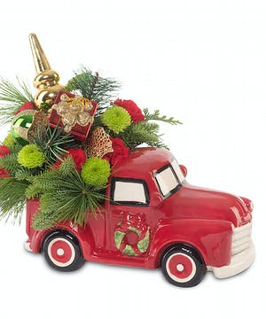 Red ceramic pickup truck with holiday arrangement