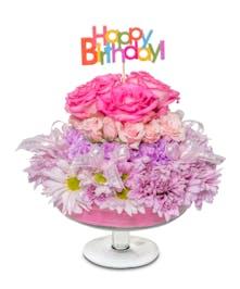 Pink themed birthday arrangement in glass pedestal vase