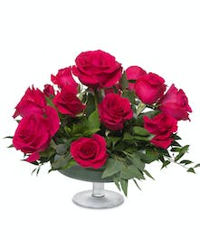 One dozen roses in a glass pedestal vase