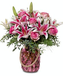 Lilies and Roses in rose-colored, faceted jar vase.