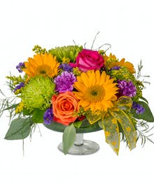 Bright summer arrangement in a glass pedestal vase
