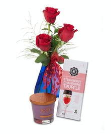 3 red short-stemmed Roses in blue glass vase with  Root candle and truffles